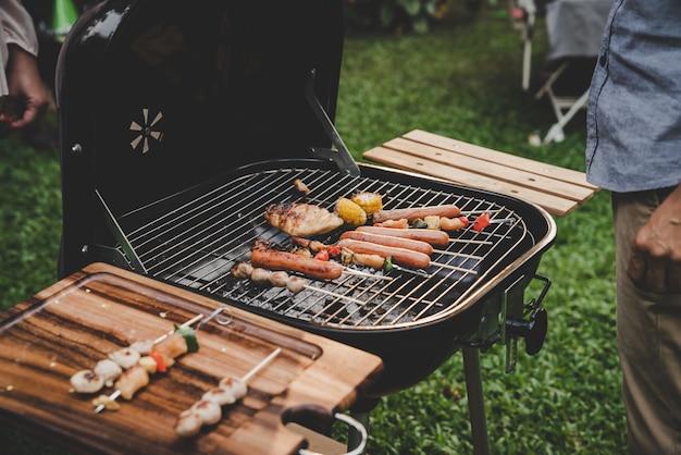 Groupe d'amis de cuisine senior barbecue sur le gril en fête à la maison jardin Photo Premium