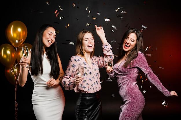 Groupe d'amis dansant entouré de confettis Photo gratuit