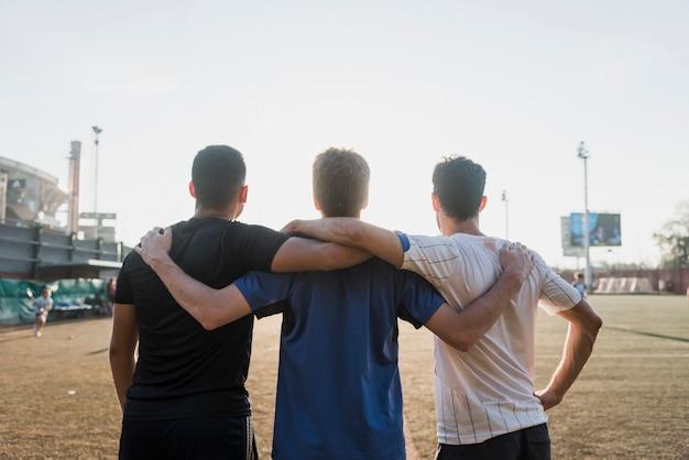 Groupe d'amis debout ensemble face au stade Photo gratuit