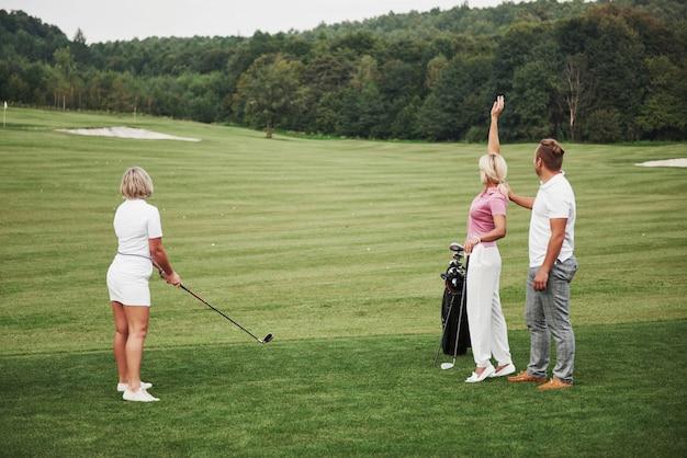 Groupe D'amis élégants Sur Le Parcours De Golf Apprennent à Jouer à Un Nouveau Jeu Photo Premium