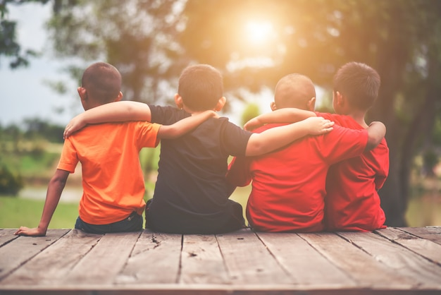 Groupe D'amis Enfants Bras Autour Assis Ensemble Photo gratuit