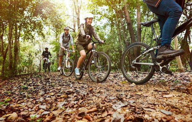 Groupe D'amis Faire Du Vélo De Montagne Dans La Forêt Ensemble Photo gratuit
