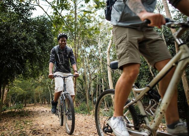 Groupe d'amis faire du vélo de montagne dans la forêt ensemble Photo Premium