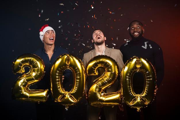 Groupe D'amis à La Fête Du Nouvel An Posant Photo gratuit