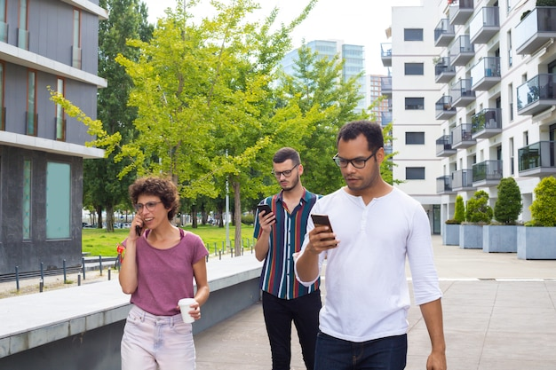 Groupe d'amis avec des gadgets se promener à l'extérieur Photo gratuit
