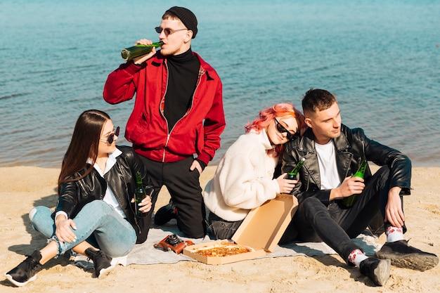 Groupe d'amis heureux ayant une fête sur la plage Photo gratuit
