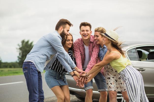 Groupe d'amis heureux, debout sur la route, mettant les mains ensemble Photo gratuit