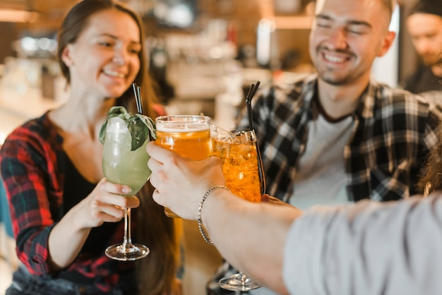 Groupe d'amis heureux griller des boissons tout en faisant la fête dans le pub Photo gratuit