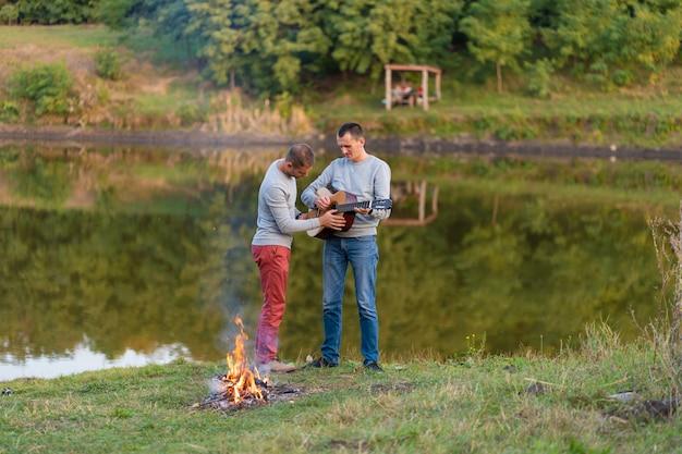Groupe D'amis Heureux Avec Guitare, S'amuser En Plein Air, Danser Et Sauter Près Du Lac Dans Le Parc Photo Premium
