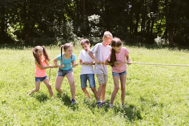Groupe d'amis jouant au tir à la corde Photo gratuit
