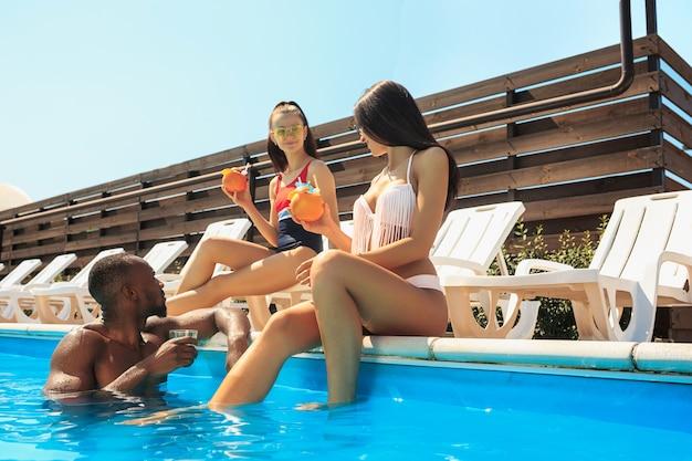 Groupe D'amis Jouant Et Se Détendre Dans Une Piscine Pendant Les Vacances D'été Photo gratuit