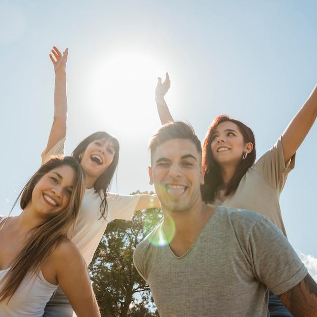 Groupe d'amis en levant les bras sur fond de ciel Photo gratuit