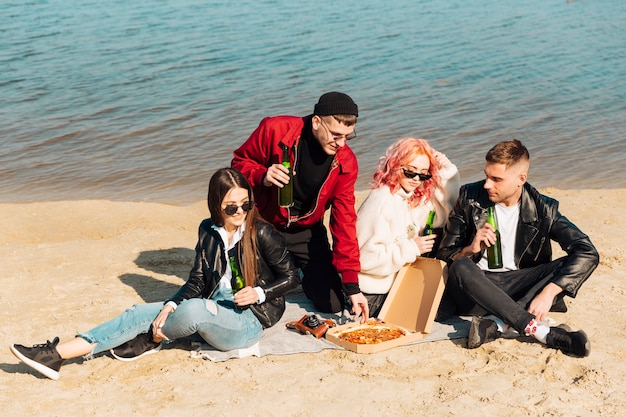 Groupe d'amis sur un pique-nique au bord de la mer Photo gratuit