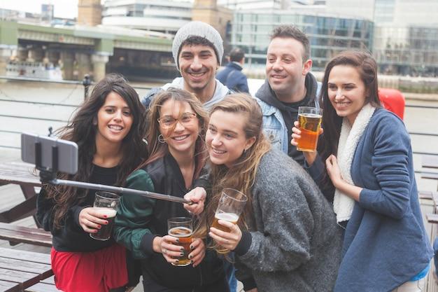 Groupe d'amis prenant un selfie au pub de londres Photo Premium