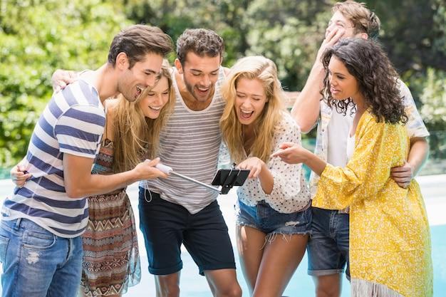 Groupe d'amis prenant un selfie près de la piscine Photo Premium