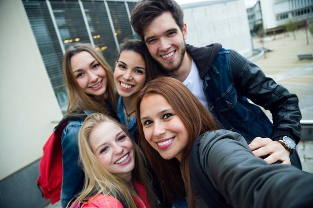 Groupe d'amis qui s'amuse dans la rue après la classe. Photo gratuit