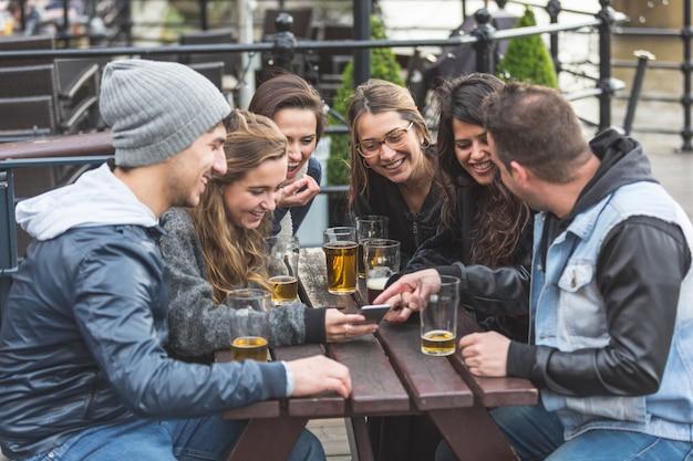 Groupe d'amis en regardant un téléphone intelligent au pub Photo Premium