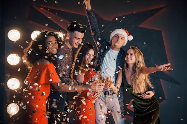 Un groupe d'amis s'amusent dans de belles robes en mousseline avec du champagne et des confettis, se préparant pour la nouvelle année Photo Premium