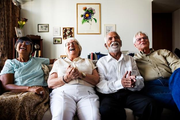 Groupe d'amis seniors assis et regardant la télévision ensemble Photo Premium