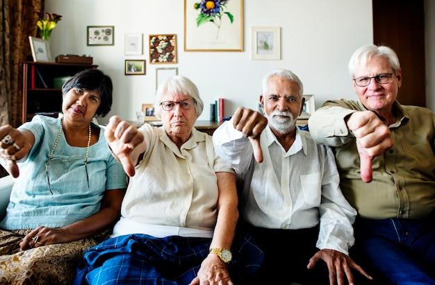 Groupe d'amis seniors gesticulant pouce vers le bas de signe Photo Premium
