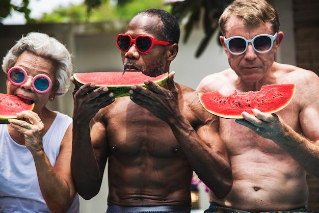 Groupe d'amis seniors manger de la pastèque au bord de la piscine Photo Premium