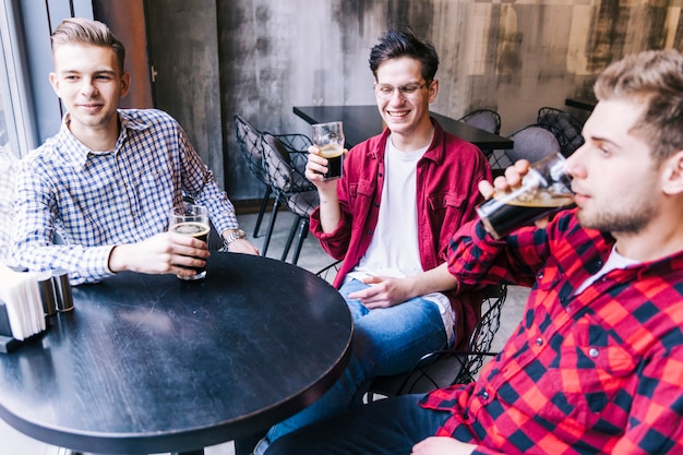 Groupe d'amis de sexe masculin assis à table appréciant la bière au bar restaurant Photo gratuit