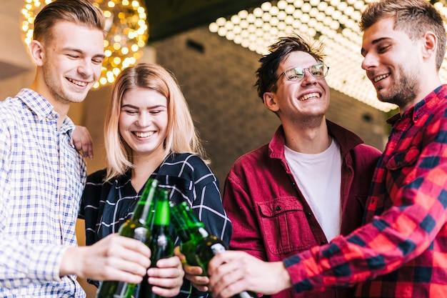 Groupe d'amis souriants portant les bouteilles de bière au pub Photo gratuit