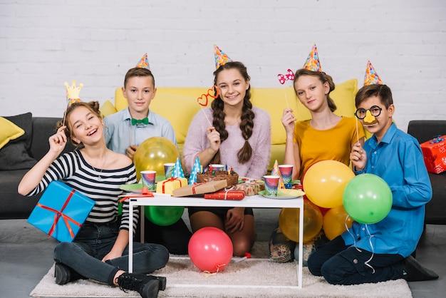 Groupe d'amis tenant l'accessoire profitant de la fête d'anniversaire Photo gratuit