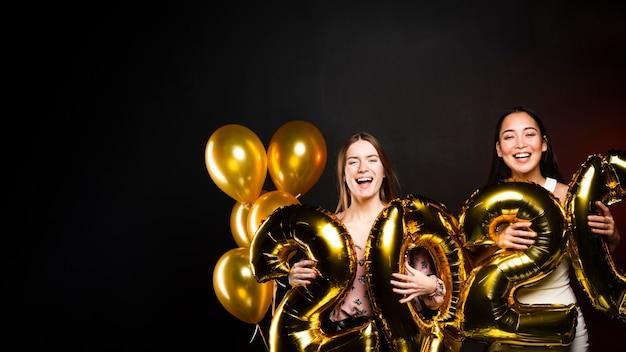 Groupe d'amis tenant des ballons d'or pour le nouvel an Photo gratuit