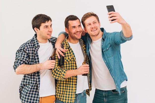 Groupe d'amis tenant une bouteille de bière prenant selfie sur téléphone portable sur fond blanc Photo gratuit