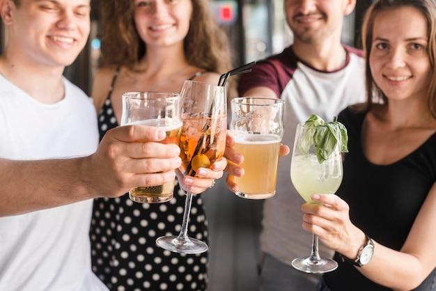 Groupe d'amis tenant différents types de boissons alcoolisées Photo gratuit