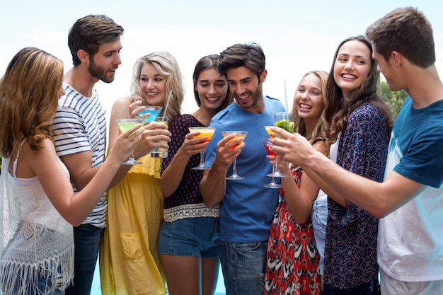 Groupe d'amis tenant un verre de cocktail au bord de la piscine Photo Premium