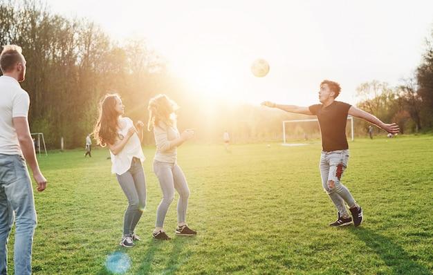 Un Groupe D'amis En Tenue Décontractée Joue Au Soccer En Plein Air. Les Gens S'amusent Et S'amusent. Repos Actif Et Coucher De Soleil Pittoresque. Photo Premium