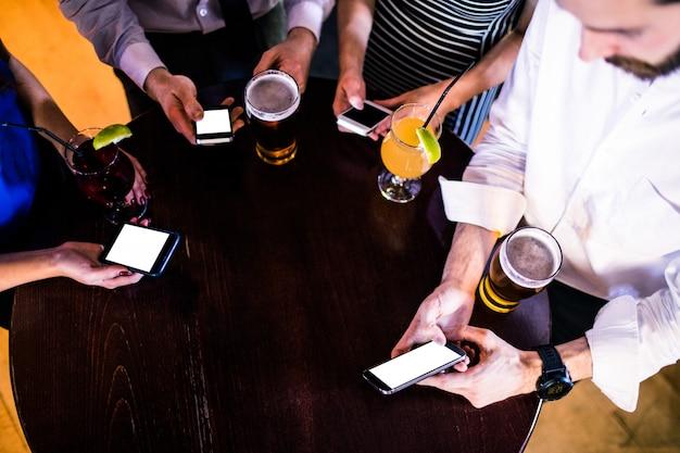 Groupe d'amis textos et prendre un verre dans un bar Photo Premium