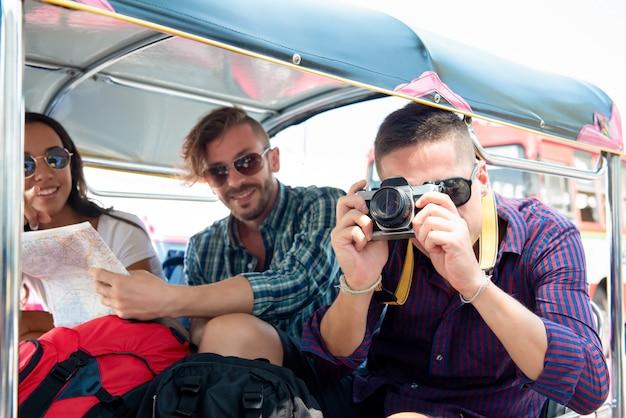 Groupe d'amis touristiques sur un taxi tuk tuk explorant la ville de bangkok, thaïlande Photo Premium