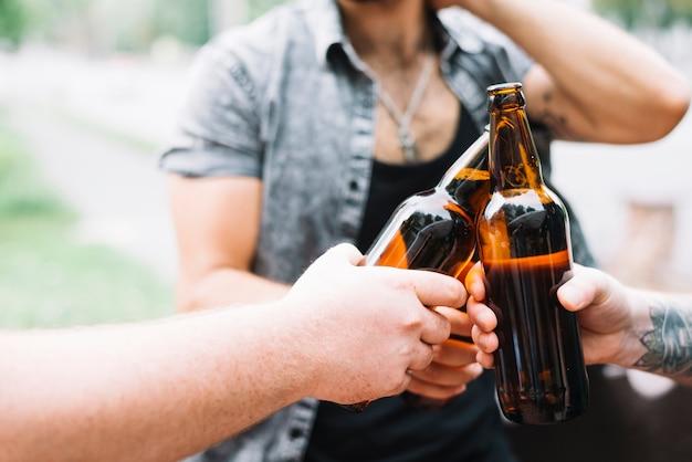 Groupe d'amis en train de faire griller des bouteilles de bière à l'extérieur Photo gratuit