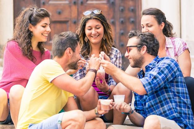 Groupe d'amis en train de manger de la glace fondante en italie Photo Premium