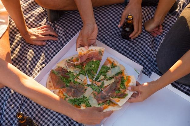 Groupe d'amis en train de manger une pizza en plein air Photo gratuit