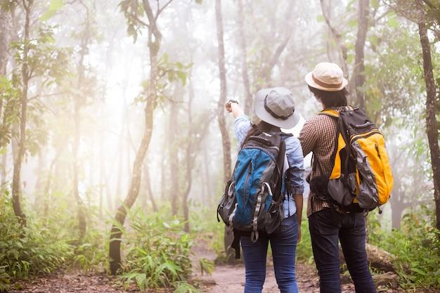 Groupe d'aventure asiatique d'amis souriants marchant avec des sacs à dos Photo Premium