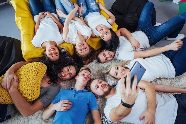 Groupe De Beaux Jeunes Faisant Selfie Allongé Sur Le Sol, Meilleurs Amis Filles Et Garçons S'amusant Ensemble, Posant Un Style De Vie émotionnel Photo Premium