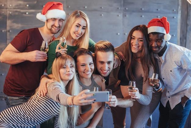 Groupe de beaux jeunes faisant selfie à la fête du nouvel an, meilleurs amis, filles et garçons, s'amusant ensemble, posant des gens émotionnels. chapeaux de pères noël et coupes de champagne à la main Photo Premium