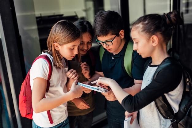 Groupe de camarades discutant de devoirs devant l'école Photo Premium