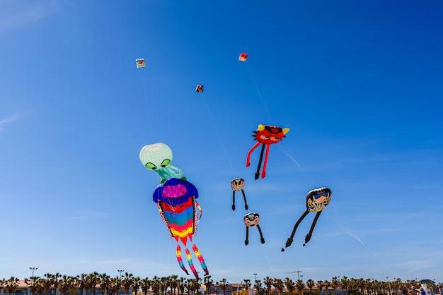 Groupe de cerfs-volants avec des formes d'animaux volant pendant un festival d'été Photo Premium
