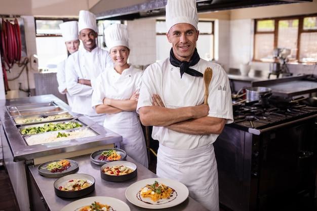 Groupe de chefs debout avec les bras croisés dans la cuisine Photo Premium