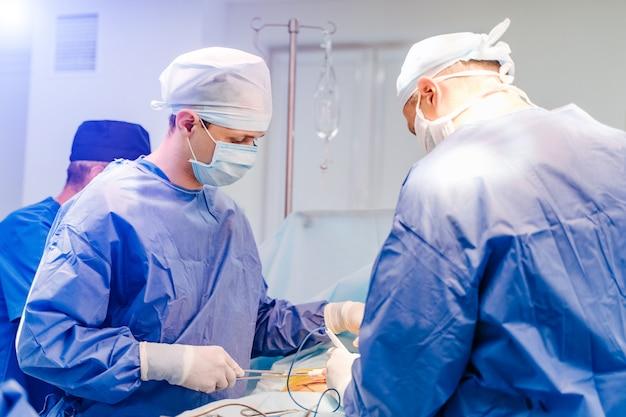 Groupe de chirurgiens en salle d'opération avec équipement chirurgical Photo Premium
