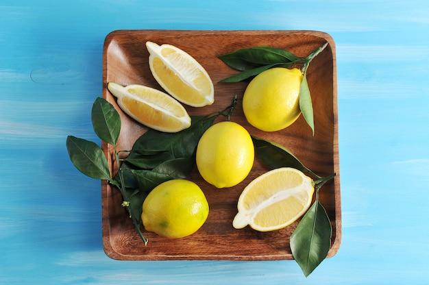 Groupe de citrons jaunes avec des feuilles sur une plaque de bois carrée sur un fond en bois bleu Photo Premium