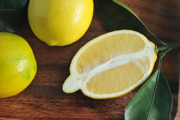Groupe de citrons jaunes avec des feuilles sur une plaque en bois Photo Premium