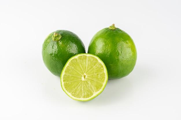 Groupe De Citrons Verts Au Citron En Tranches Sur Fond Blanc. Photo Premium