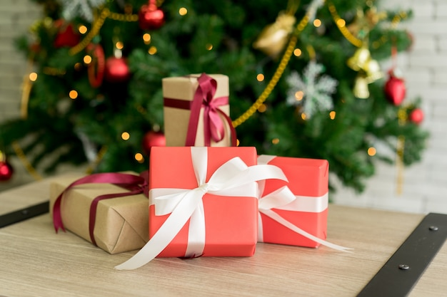 Groupe de coffrets cadeaux sur une table en bois décoré d'un sapin de noël Photo Premium