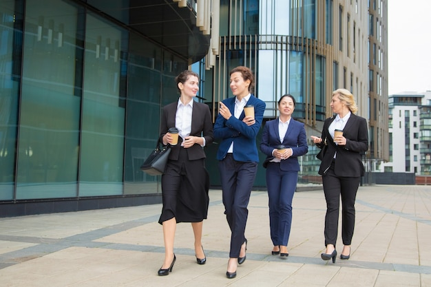Groupe De Collègues De Travail Marchant Avec Du Café à Emporter à L'extérieur, Parler, Souriant. Pleine Longueur, Vue De Face. Concept De Pause De Travail Photo gratuit